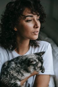 crop woman with cat looking away